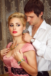 young man puts on jewelry on beautiful woman
